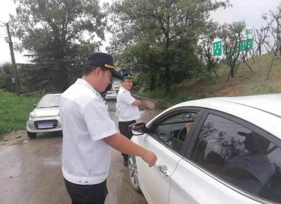 大雨挡不住志愿者的脚步 指挥交通保安全